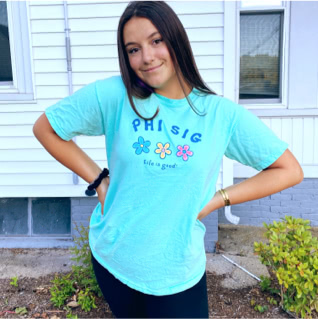 Phi Sigma member wearing a Life is Good t-shirt with image of three flowers