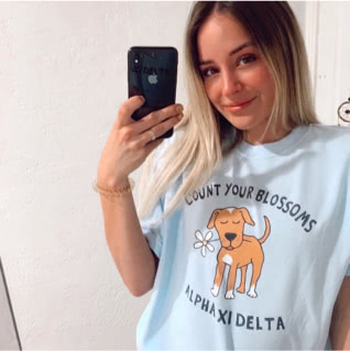 Alpha Xi Delta member wearing Life is Good t-shirt with an image of a dog and flower